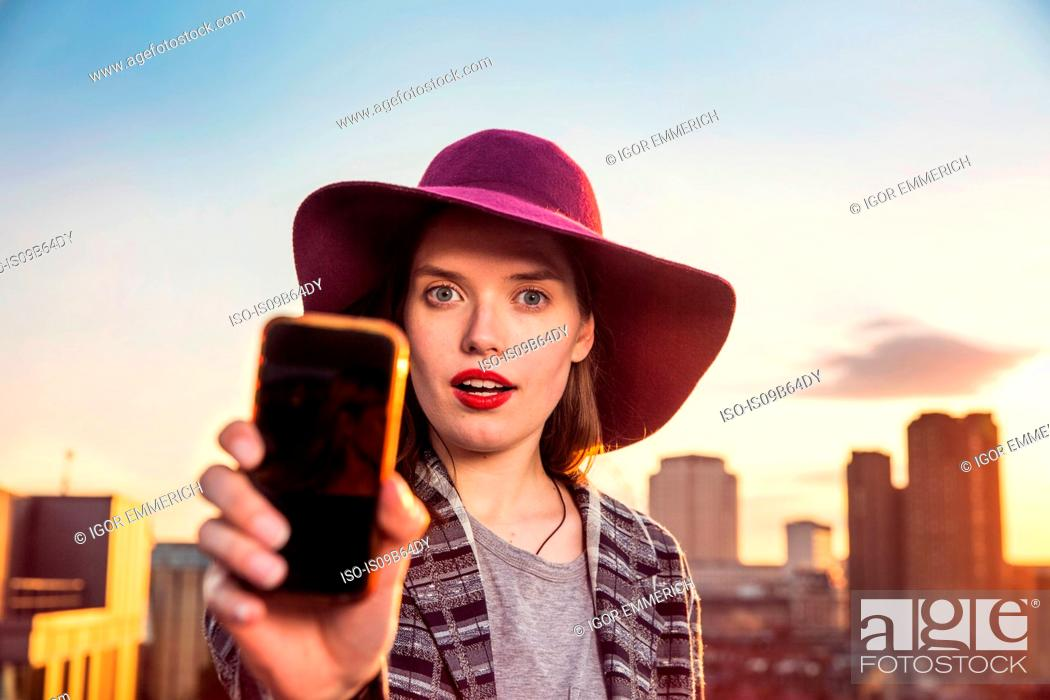 Photo de stock: Portrait of young woman taking smartphone selfie at sunset roof party in London, UK.