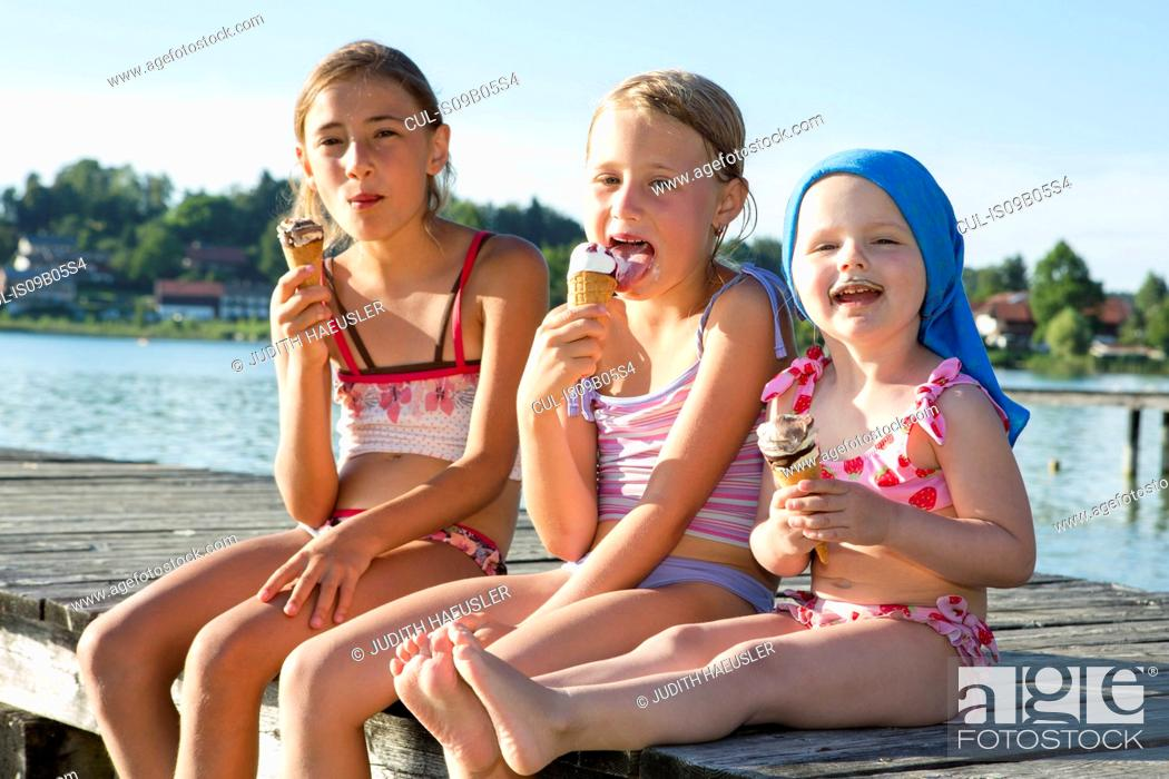 Stock Photo: Two sisters and female toddler on pier eating ice cream cones, Lake Seeoner See, Bavaria, Germany.