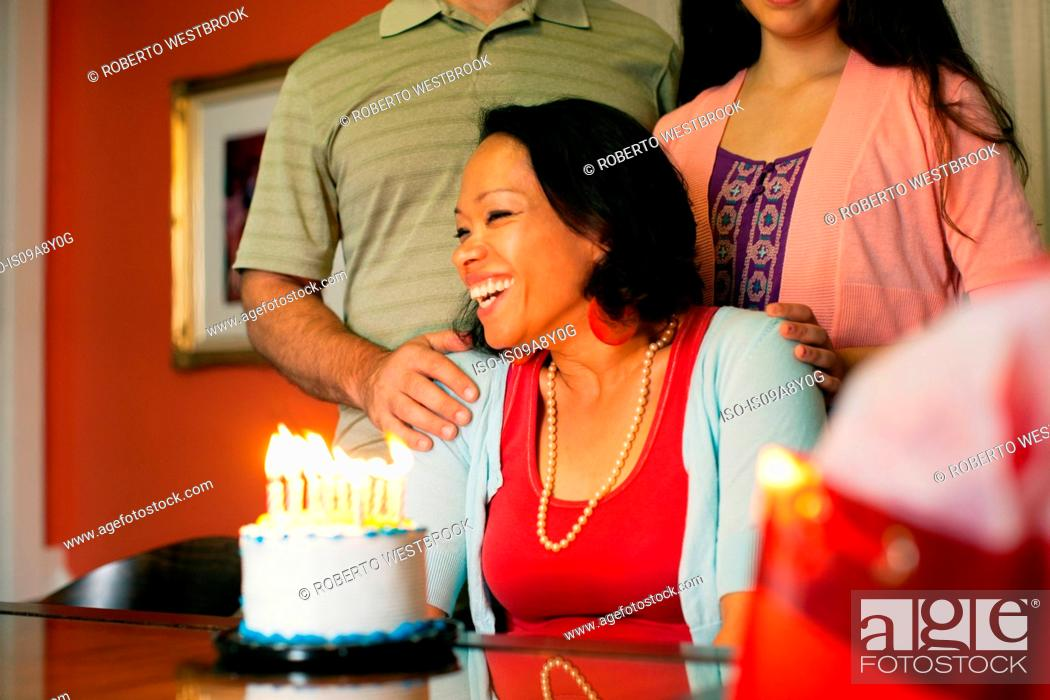 Stock Photo: Woman smiling over birthday cake.