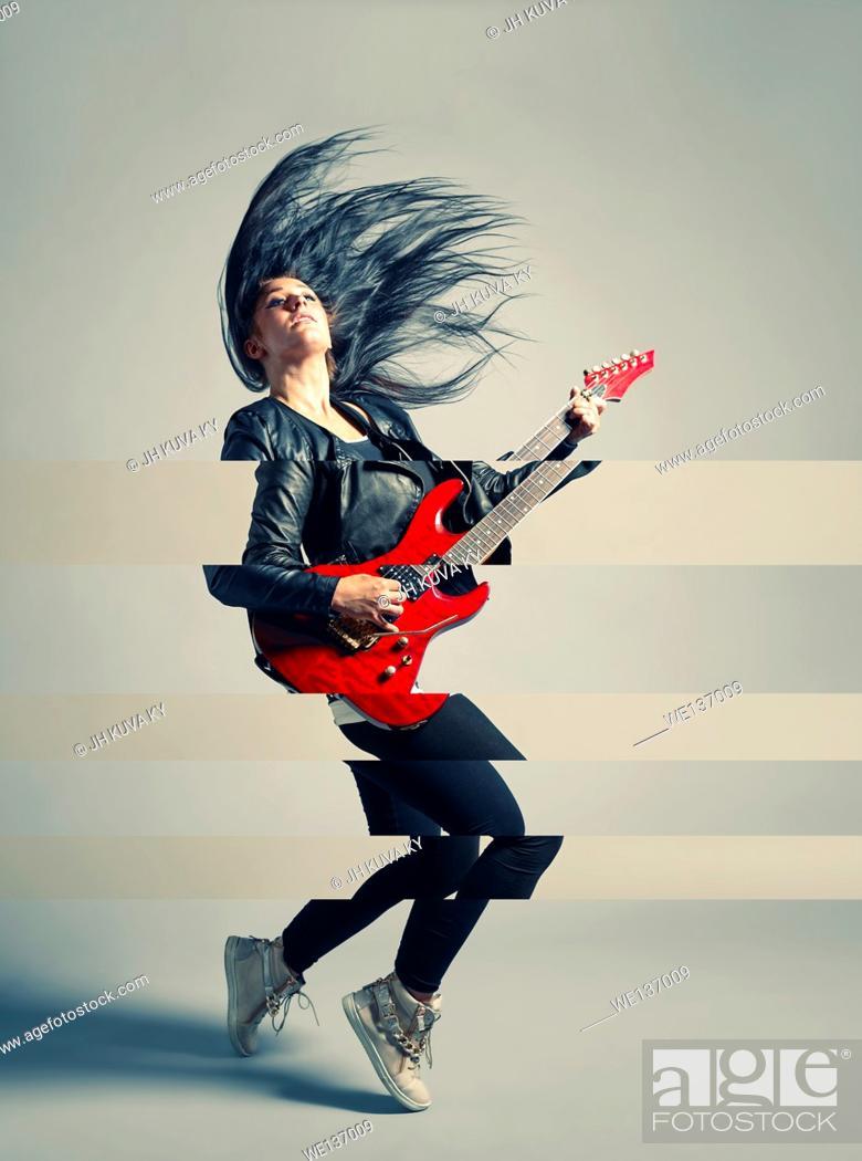 Stock Photo: Woman rocker and an electric guitar, studio shot, cross processed image.