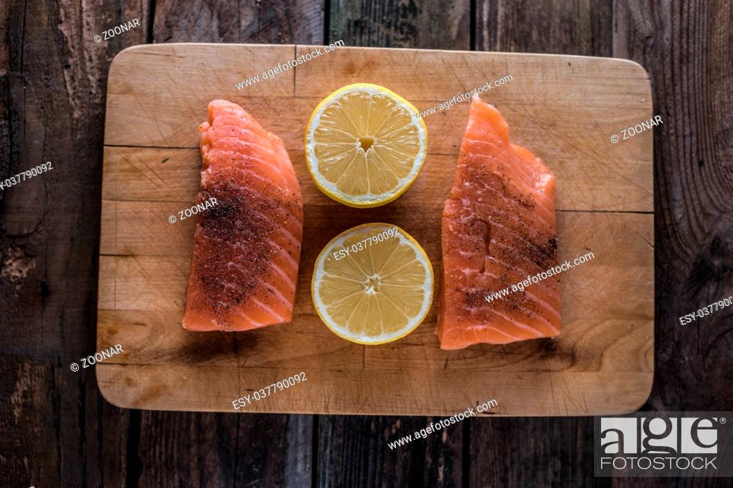 Stock Photo: raw salomon on chopping board with lemon.