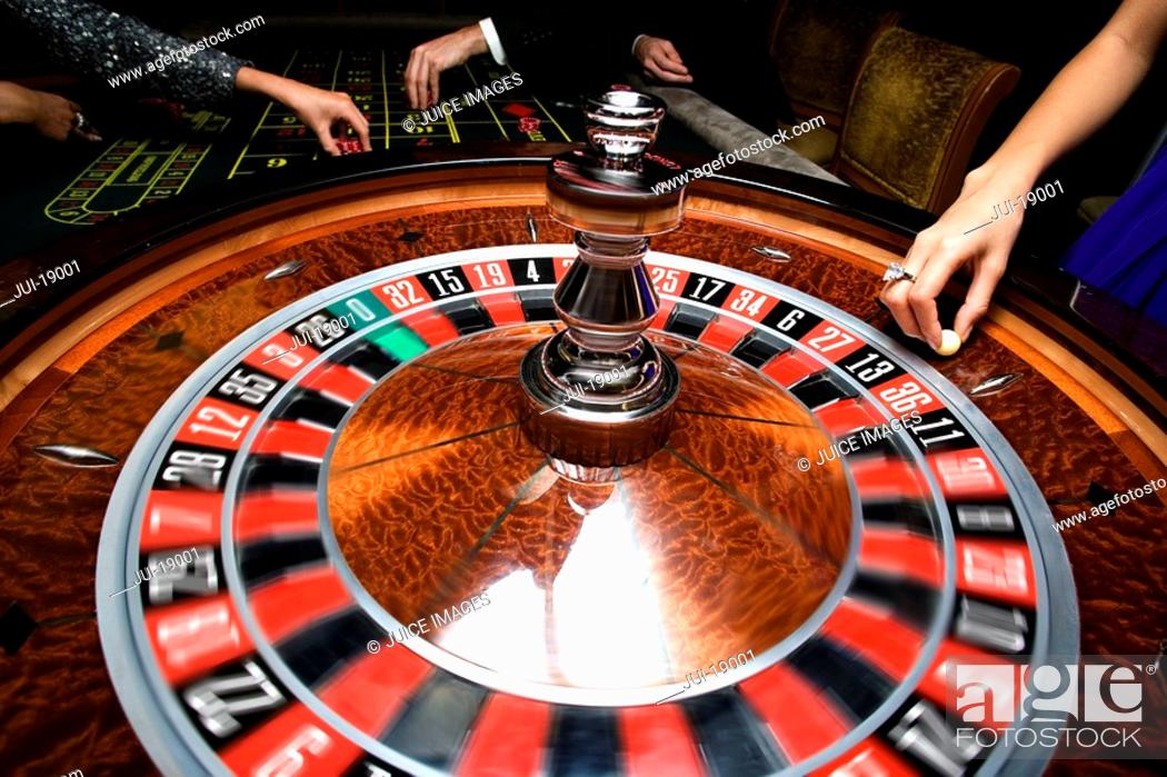 Stock Photo: People gambling at roulette table, mid section.