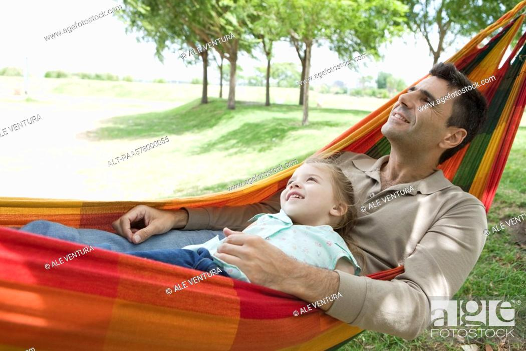 Stock Photo: Father and young daughter relaxing together in hammock.