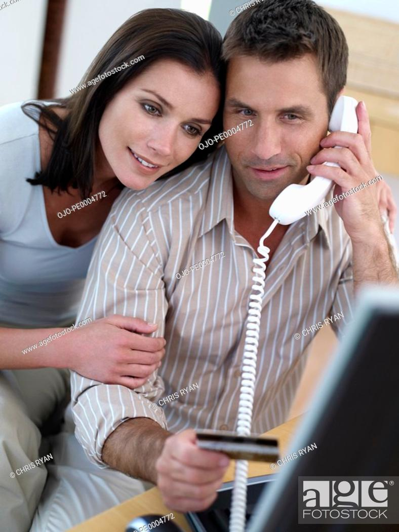 Stock Photo: Man with credit card and computer with woman.