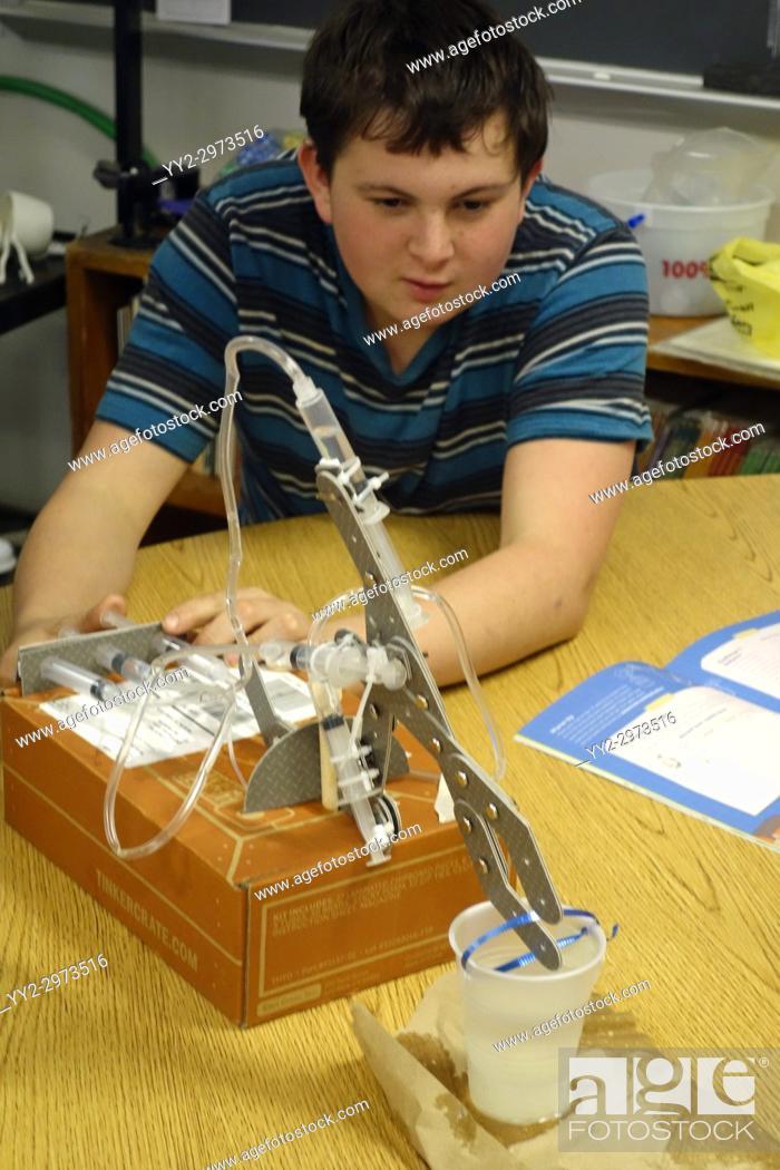 Stock Photo: 8th Grade Boy Manipulating Hydraulic Claw Kit, Wellsville, New York, USA.
