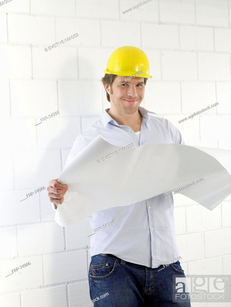 Stock Photo: Man wearing helmet with construction plans.