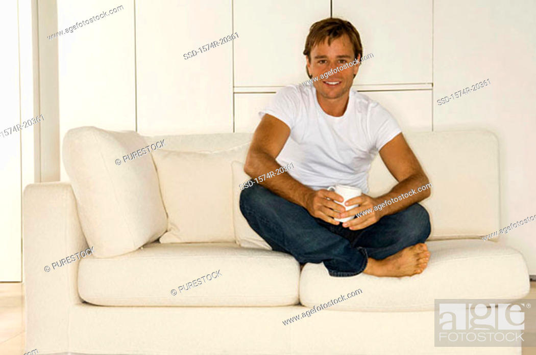 Stock Photo: Portrait of a young man sitting on a couch and smiling.