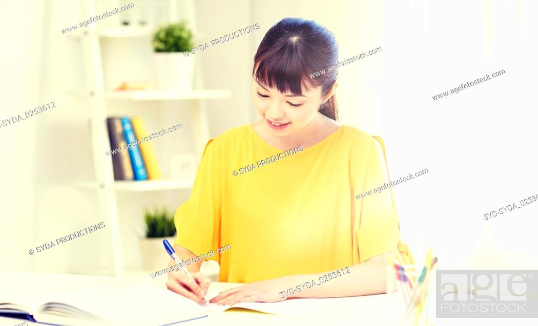 Stock Photo: happy asian young woman student learning at home.