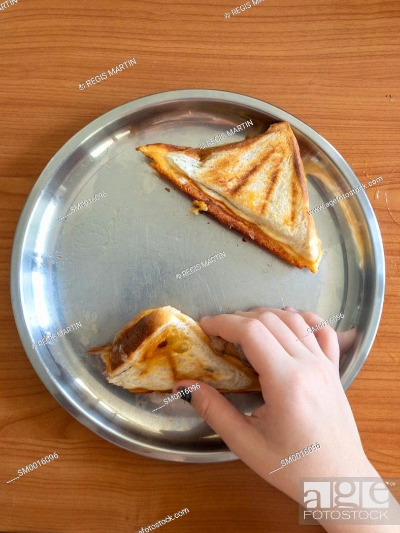 Stock Photo: Personal point of view of a child taking a toasted sandwich from a stainless steel plate.