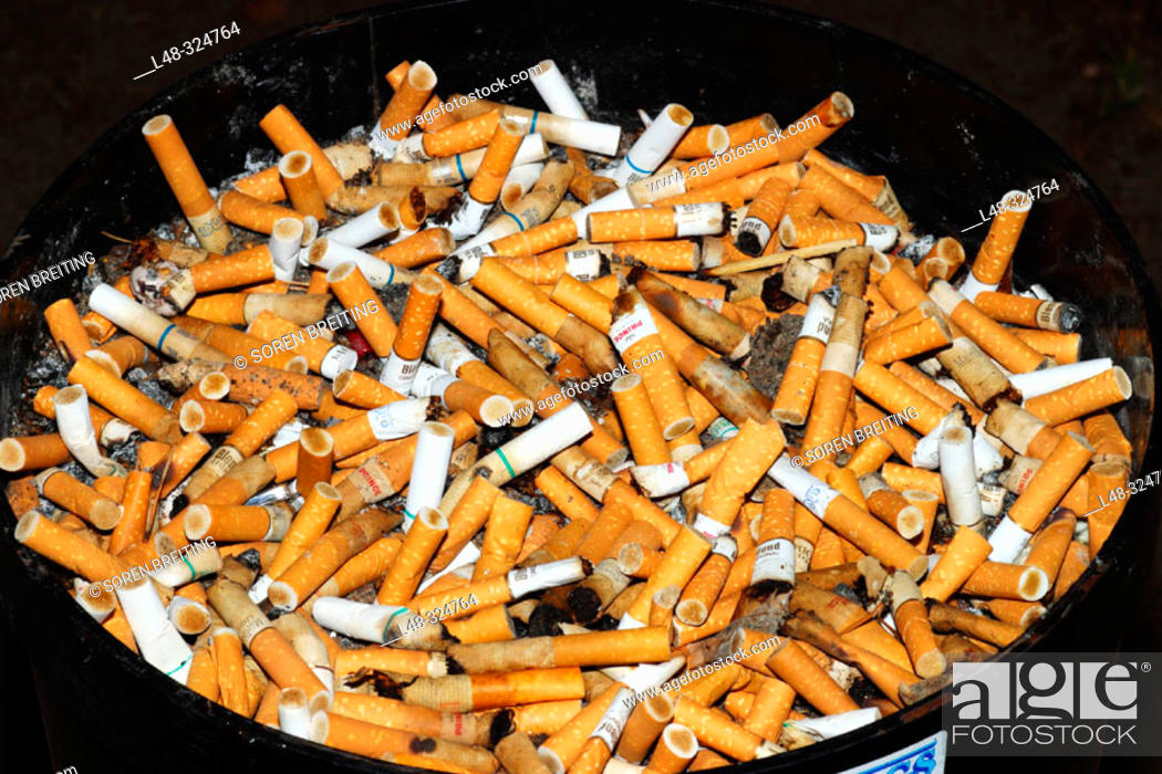 Stock Photo: A diversity of filter cigarettes as cigarette butts in a huge ashtray in the outdoors in a special allocated smoking space for smokers.