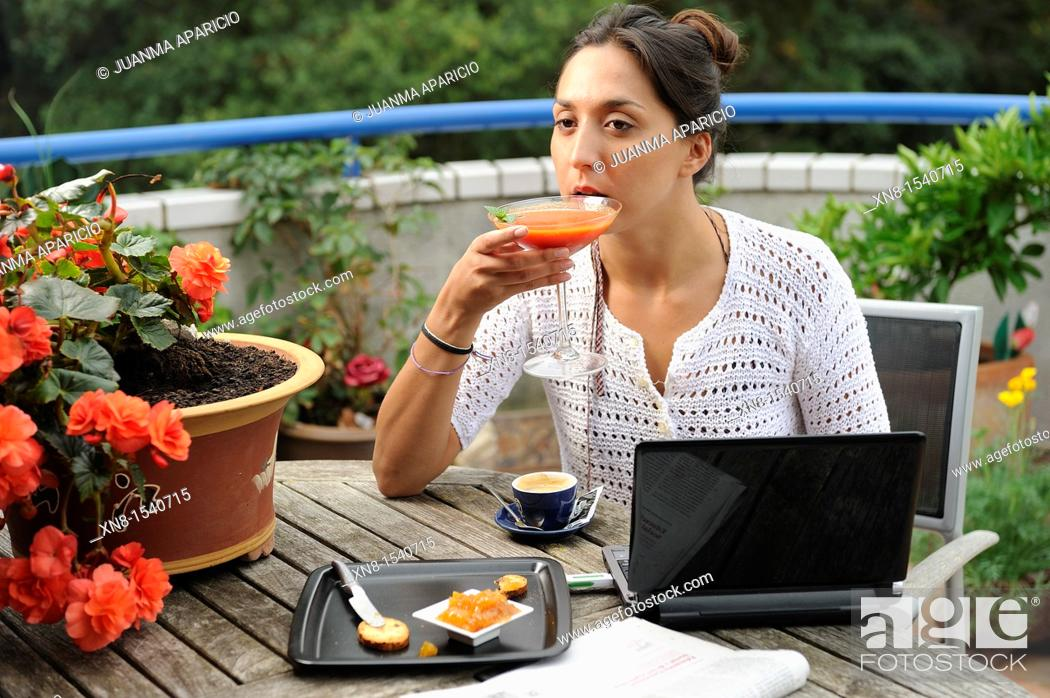 Stock Photo: Young woman having breakfast on a terrace.
