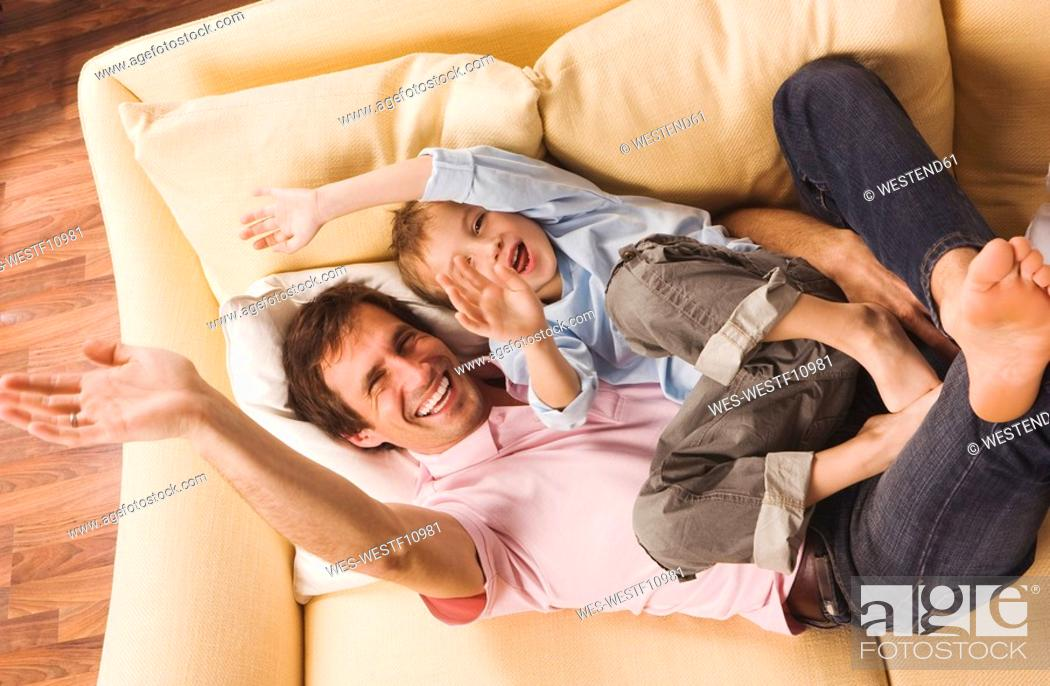 Stock Photo: Father and son 4-5, fooling about, waving hands, elevated view.