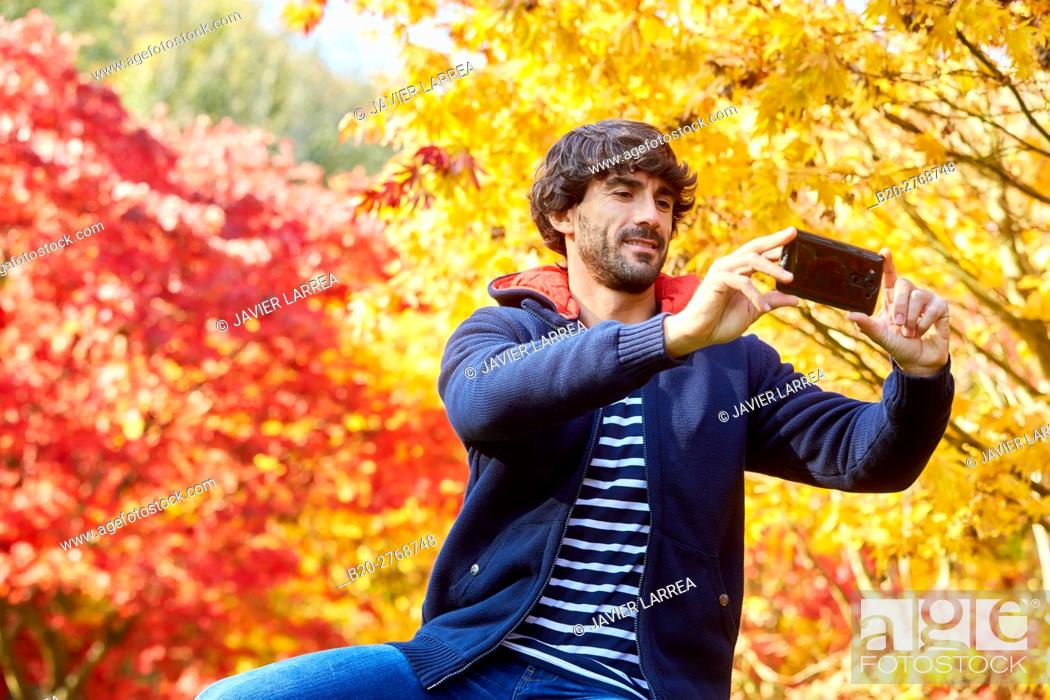 Stock Photo: Selfie, Man in the forest making a photo with smartphone, Trees in Autumn, Pagoetako Parke Naturala, Pagoeta Natural Park, Aya, Gipuzkoa, Basque Country, Spain.