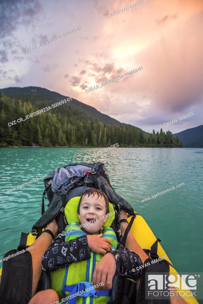 Photo de stock: Young boy smiles, laughs during father son paddling trip.