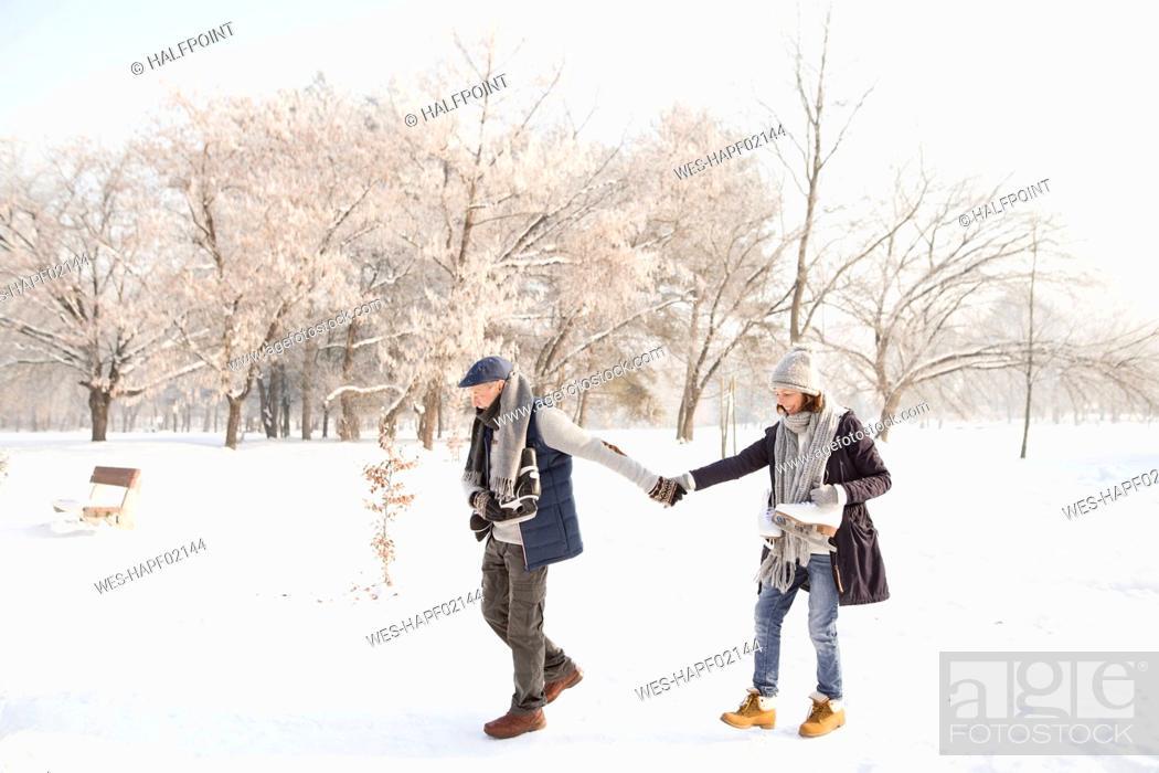 Stock Photo: Senior couple with ice skates walking in winter landscape.