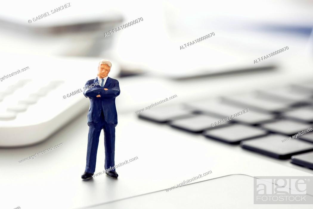 Stock Photo: Businessman figurine standing on laptop computer keyboard.