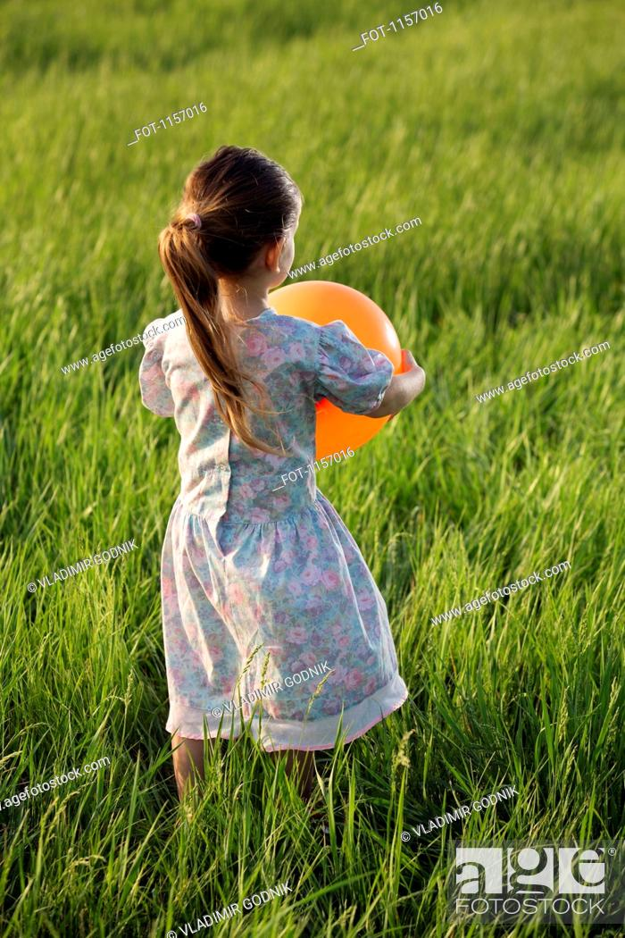 Stock Photo: Rear view of a girl holding a balloon in a field.