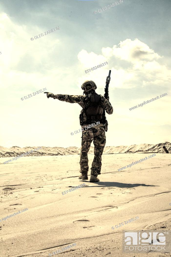 Imagen: Soldier of special forces, infantry rifleman in military ammunition walking in desert and pointing on horizon. Military reconnaissance team leader managing dead.
