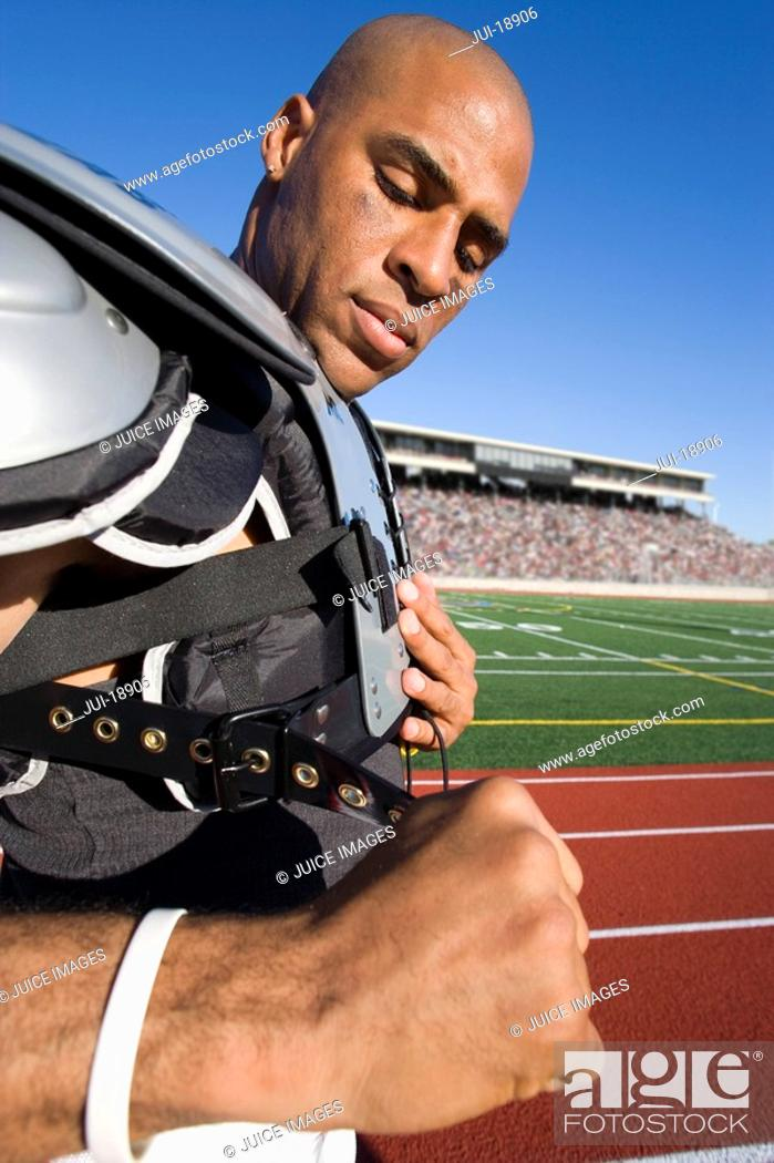 Stock Photo: Football player putting pads on.