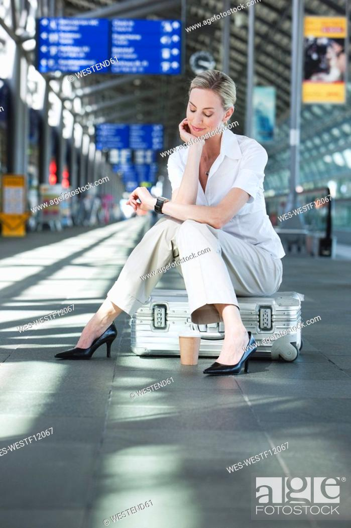 Stock Photo: Germany, Leipzig-Halle, Young woman in Airport departure lounge, sitting on suitcase.