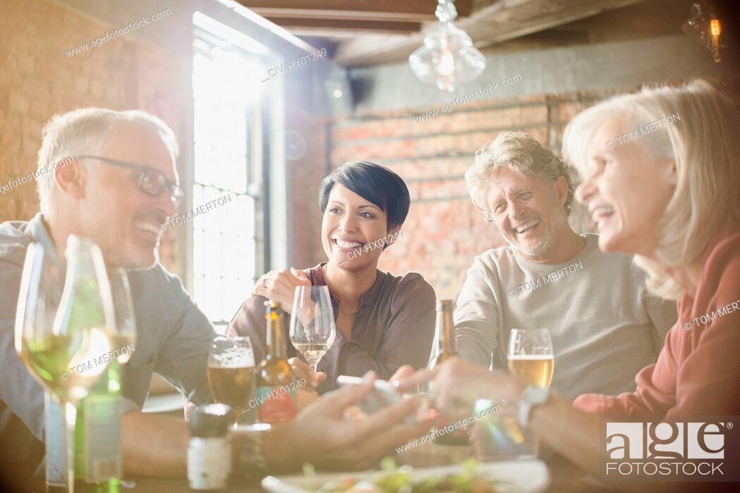 Stock Photo: Couples dining and using cell phone at restaurant table.