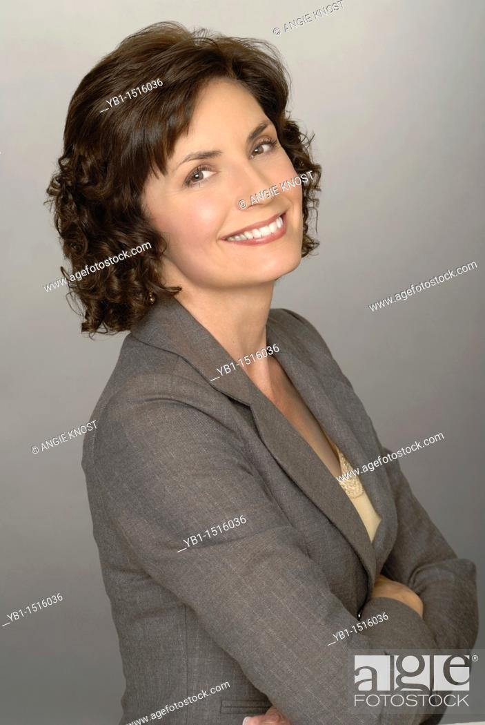 Stock Photo: Attractive business woman portrait, smiling and looking at camera or viewer.