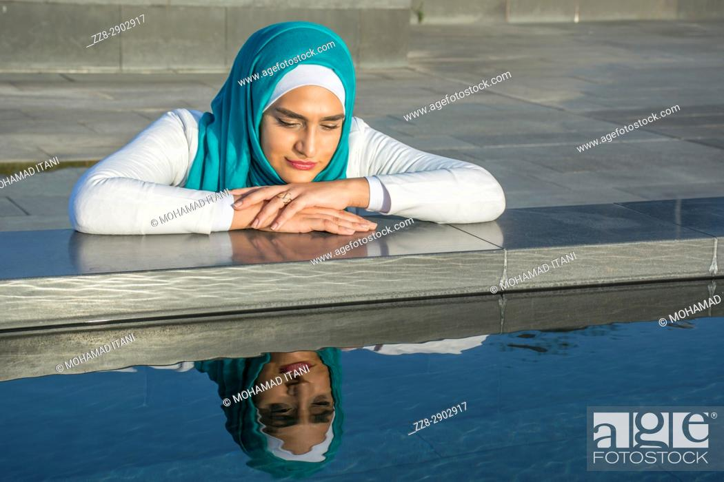 Stock Photo: Young Muslim woman wearing hijab leaning on the pool.