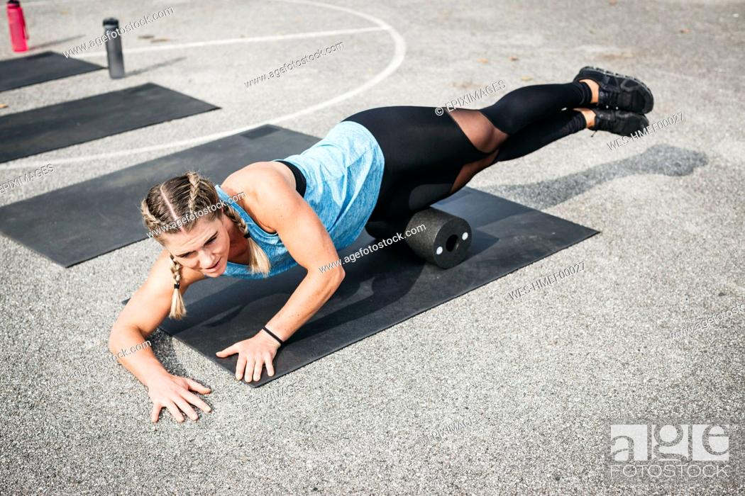 Stock Photo: Woman doing workout exercise with fascia roll outdoors.
