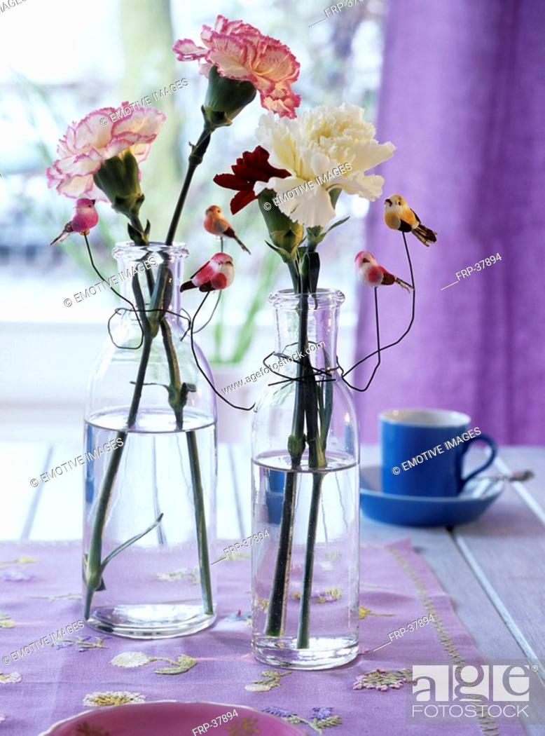 Stock Photo: Carnations in glass bottles decorated with artificial birds.
