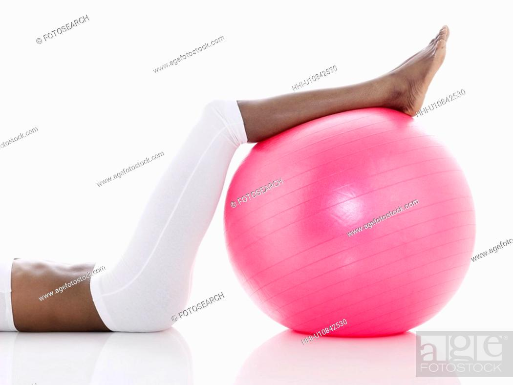 Stock Photo: Woman exercising with Swiss ball (low section).