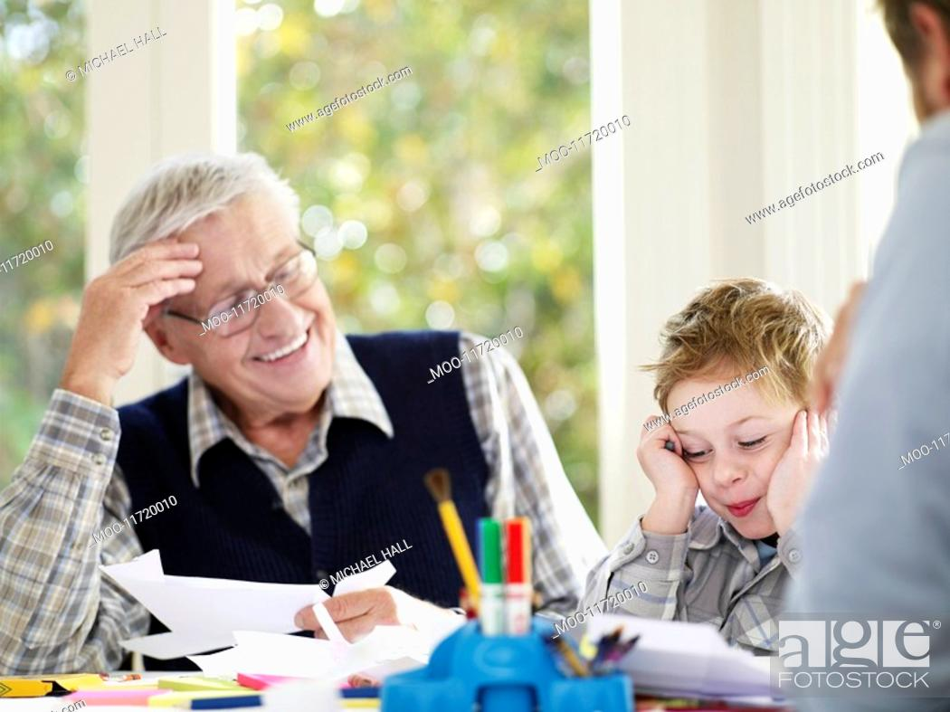 Stock Photo: Boy 3-4 laughing with father and grandfather in house.