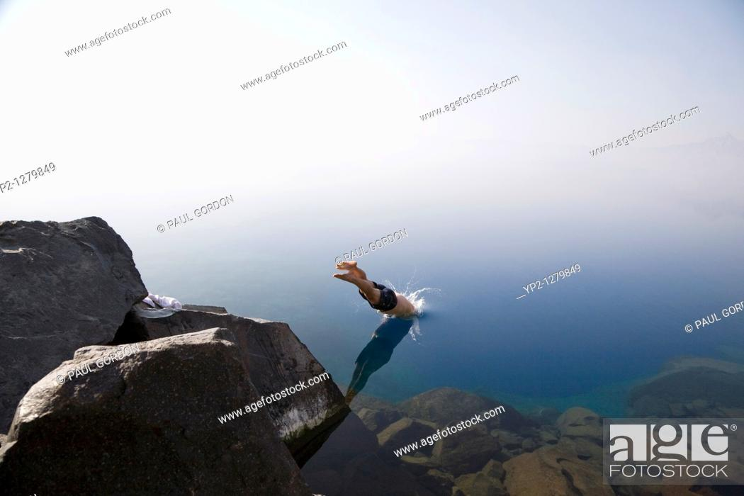 Stock Photo: Man diving from the rocks at Cleetwood Cove  Series two of three  Morning mist obscures the rim and horizon line - Crater Lake National Park Oregon - Diving.