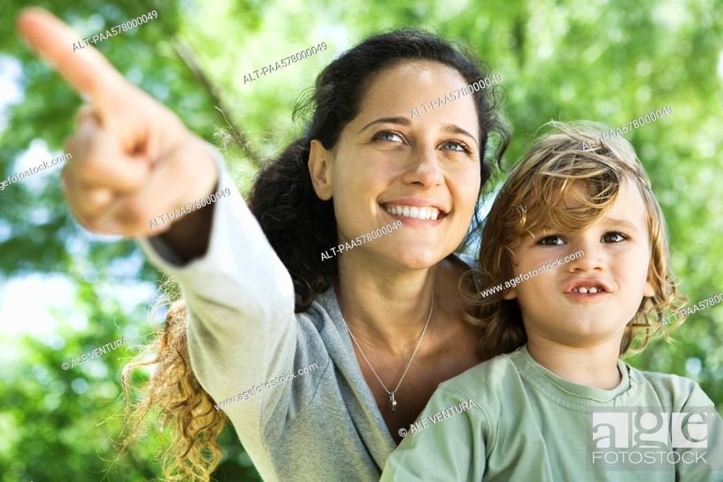 Stock Photo: Mother pointing out something to young son outdoors.