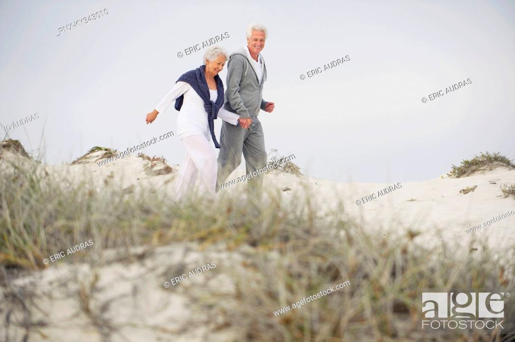 Stock Photo: Senior couple walking on the beach.