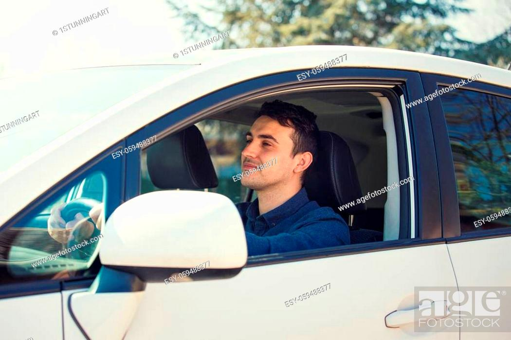 Stock Photo: Successful young man driving his new white car keeps hand on the steering wheel looking ahead happy feeling safe. Confident businessman smiling.