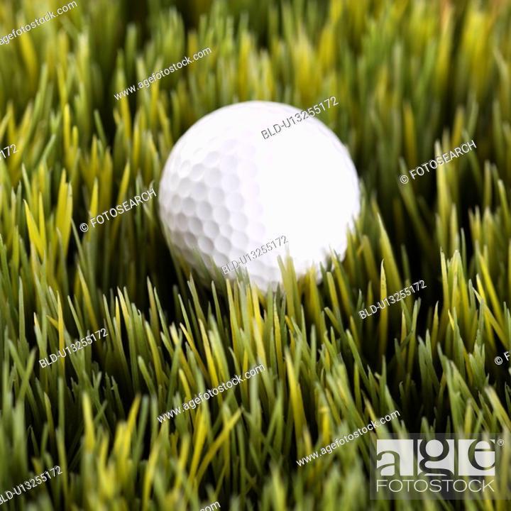Stock Photo: Studio shot of golf ball resting in grass.
