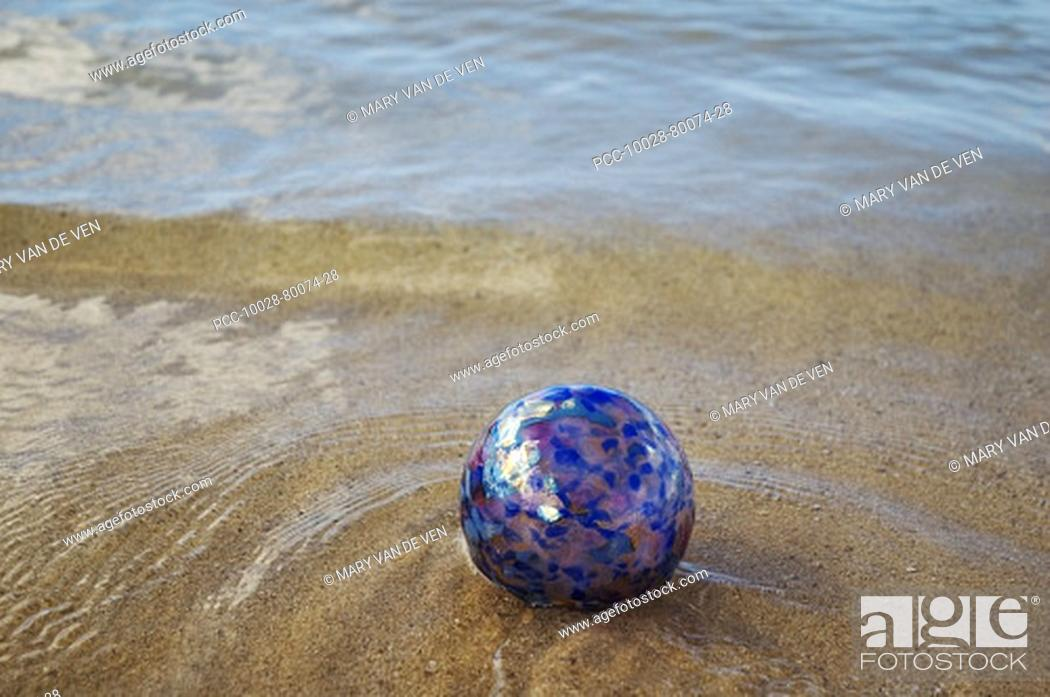 Stock Photo: Art glass float in shallow ocean water sandy beach.
