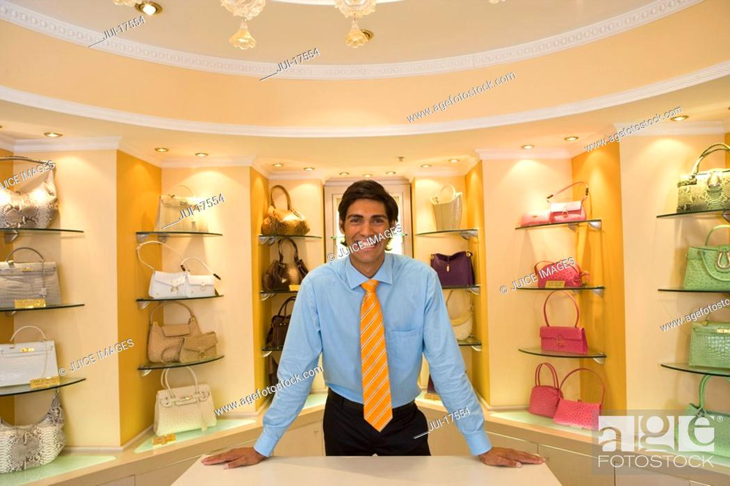 Stock Photo: Salesman posing in front of purses.