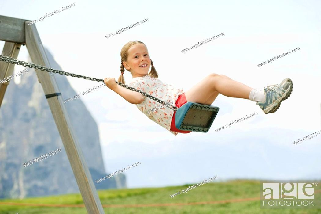 Stock Photo: Italy, Seiseralm, Girl 6-7 sitting on swing, portrait.