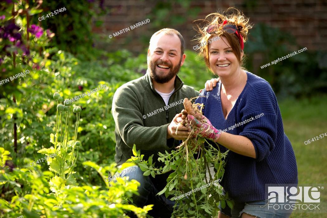 Photo de stock: Portrait happy couple harvesting fresh vegetables in sunny garden.