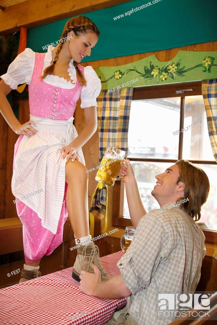 Stock Photo: Young woman standing on table at Oktoberfest, Munich, Germany.