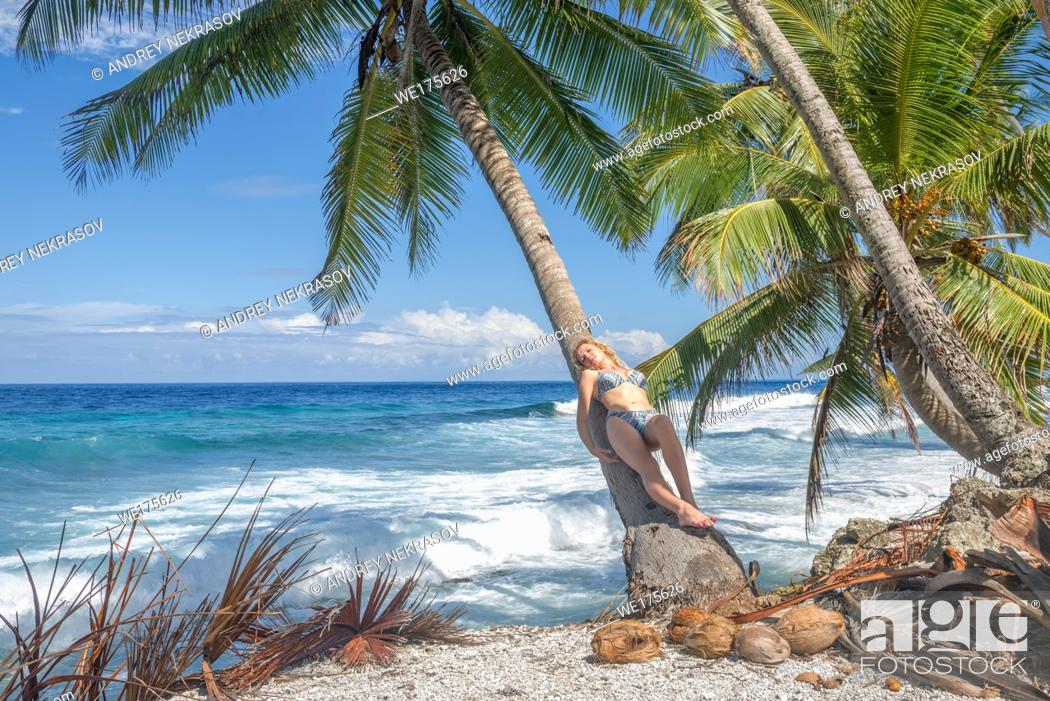 Stock Photo: Relaxing woman lies on the coconut palm tree on a tropical beach. Young beautiful woman lying on the palm tree on sea shore.