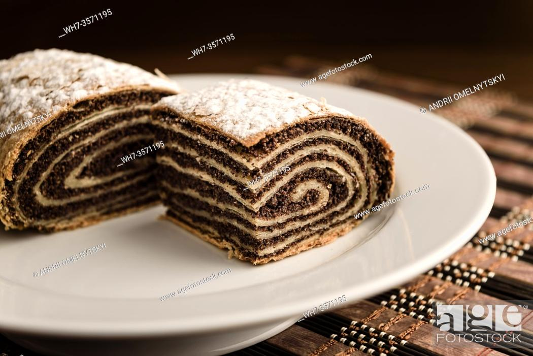 Stock Photo: strudel with poppy seeds on a ceramic white plate on wooden background.