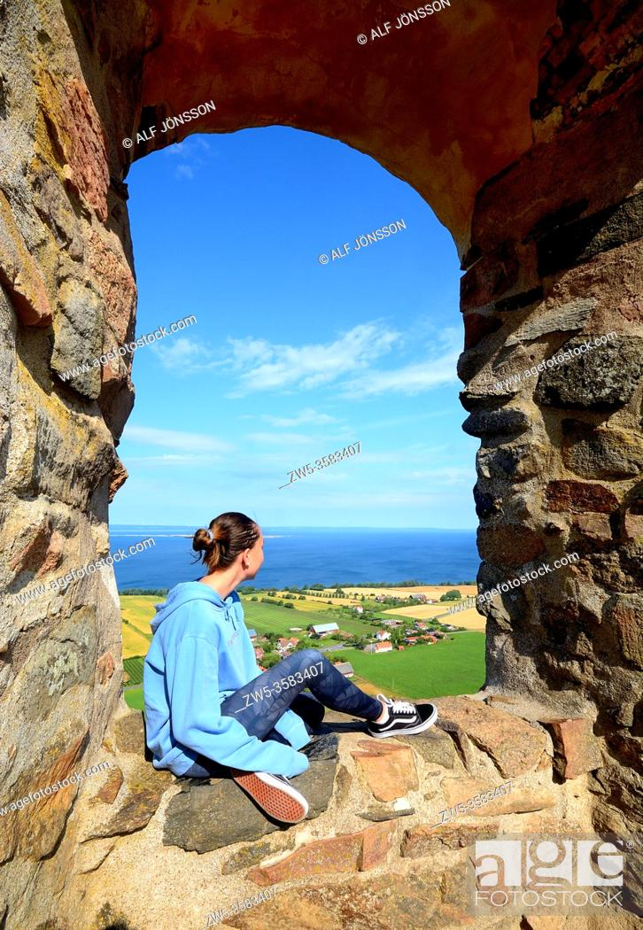 Photo de stock: Girl sitting in a window in Brahehus Castle ruin, which is situated outside Graenna in Joenkoeping County in the province of Smaland, Sweden.