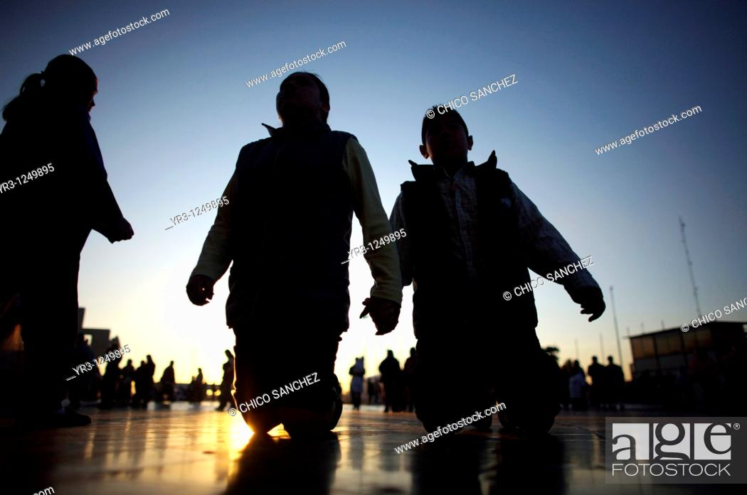Stock Photo: Pilgrims walk on their knees toward the Basilica of Guadalupe at sunrise in Mexico City. Hundreds of thousands of Mexican pilgrims converged on the Basilica.
