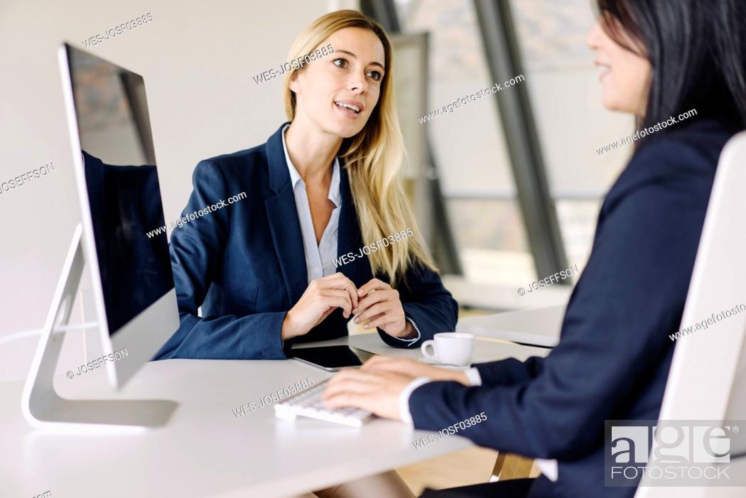 Stock Photo: Two businesswomen sitting at desk in office talking.