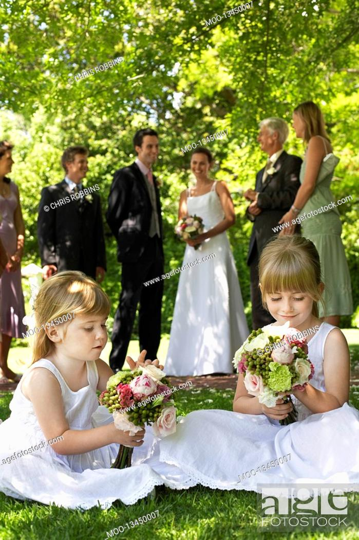 Stock Photo: Two young girls sitting on lawn holding bouquets bride and groom in background.