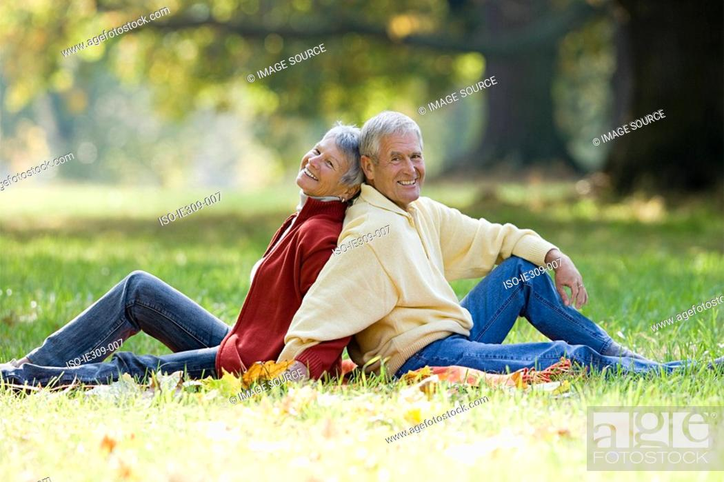 Stock Photo: Senior couple sitting back to back in a park.