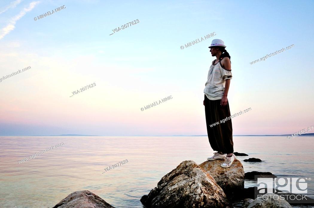 Stock Photo: Woman standing on rock watching sunset, Island Pag, Croatia, Europe.