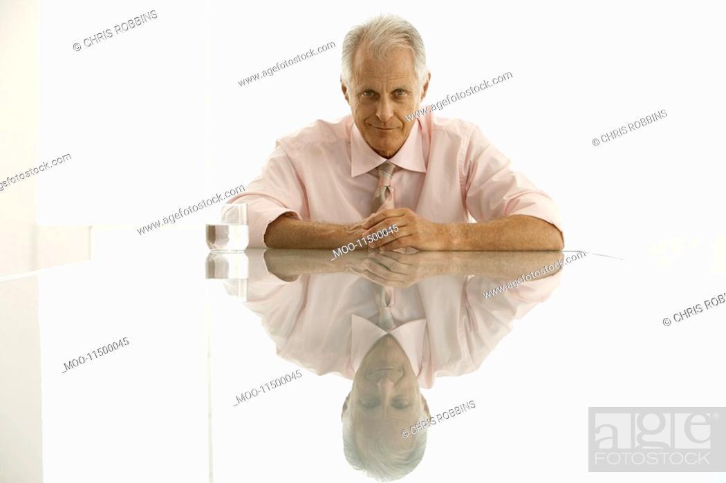 Stock Photo: Businessman sitting at table portrait.